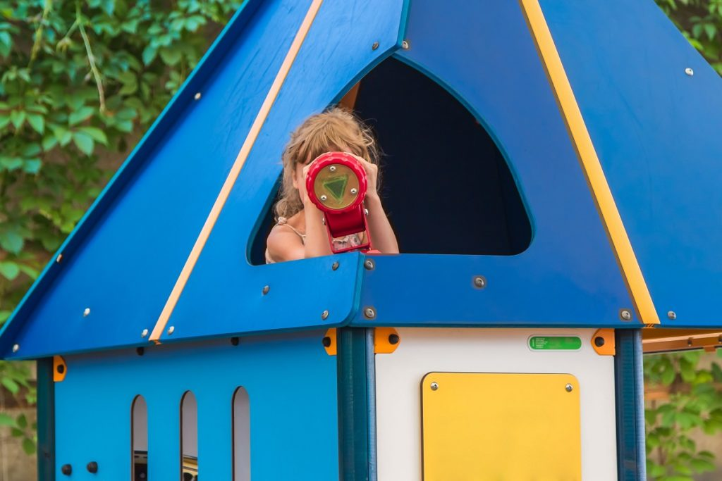 Girl using a telescope in a playhouse