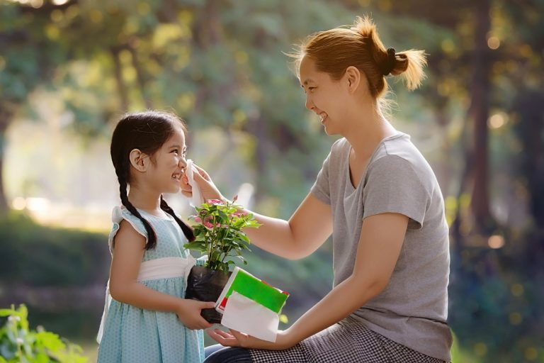 Kid holding a plant with her mom
