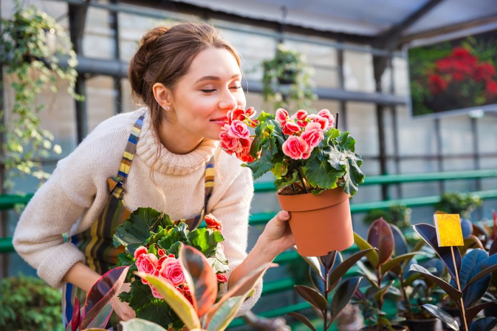Woman smelling flowers at a greenhouse