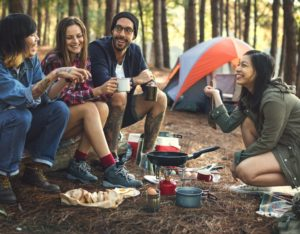 group of friends eating in their camp site