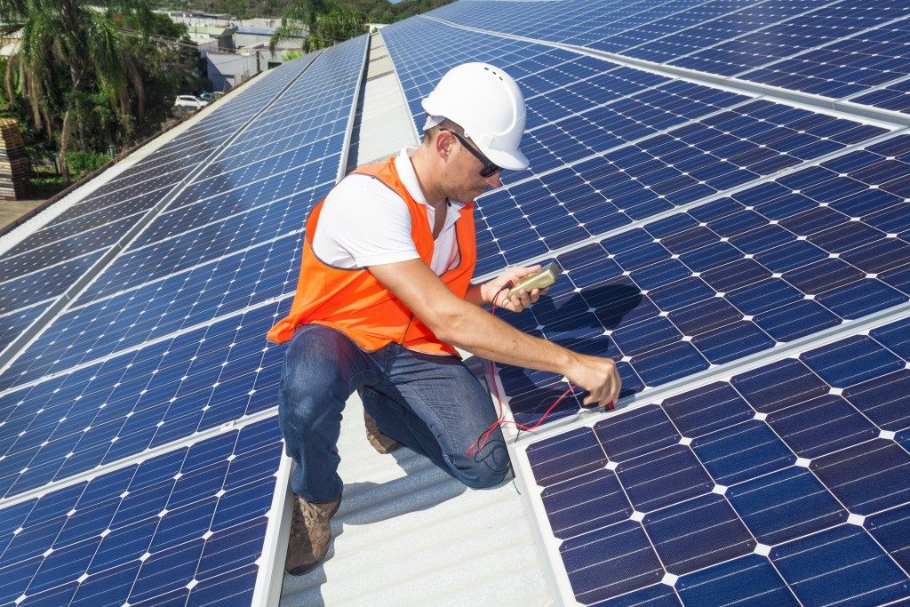 Young technician checking solar panels on the roof